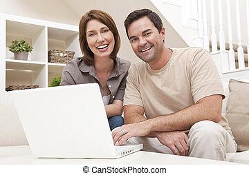 Ein glückliches Paar, das Laptop-Computer zu Hause benutzt
