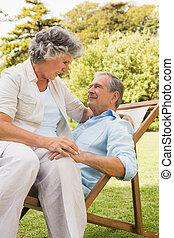 Ein glückliches, reifes Paar, das auf der Sonnenhalle sitzt