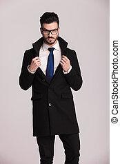 Ein gut aussehender Geschäftsmann trägt einen langen schwarzen Mantel.