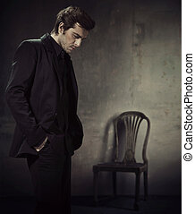 Ein gut aussehender Mann in einem Anzug im dunklen Hintergrund