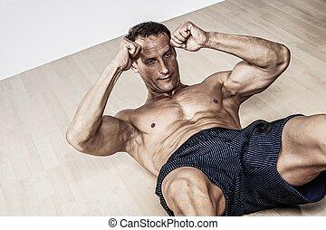 Ein gut aussehender Muskelmann macht Fitnessübungen.