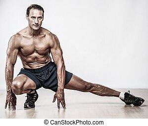 Ein gut aussehender muskulöser Mann macht Stretchingübung.