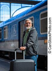 Ein gut aussehender Senior-Mann nimmt einen Zug.