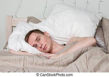 Ein hübscher junger erwachsener Mann, der im Bett schläft. Der Sexy-Typ ruht sich aus