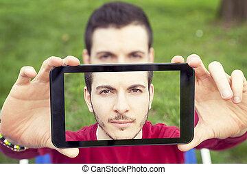 Ein hübscher junger Erwachsener nimmt einen Selbsti mit Smartphone.