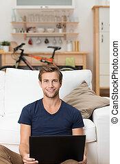 Ein hübscher junger Mann, der an einem Laptop arbeitet