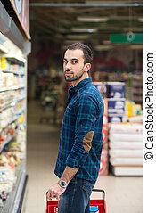 Ein hübscher junger Mann, der in einem Supermarkt einkauft.