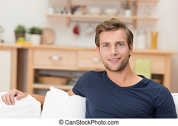 Ein hübscher junger Mann, der sich zu Hause entspannt