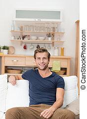 Ein hübscher junger Mann sitzt auf einem Sofa