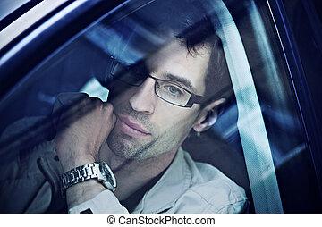 Ein hübscher Mann sitzt in einem Auto