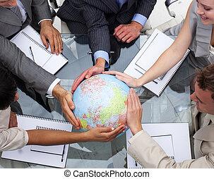 Ein hoher Winkel des Geschäftsteams mit einem terrestrischen Globus
