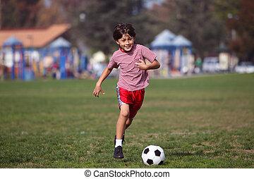 Ein Junge, der im Park Fußball spielt