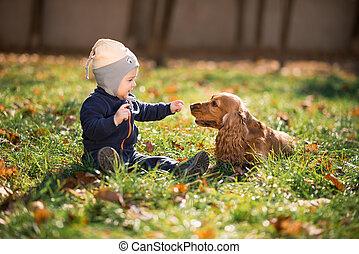 Ein Junge, der mit einem Hund auf dem Rasen sitzt.