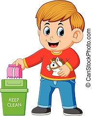 Ein Junge hält saubere Umgebung, indem er in Mülleimer spritzt.