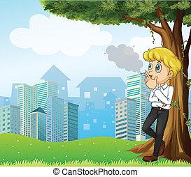 Ein Junge raucht unter dem Baum über den Gebäuden