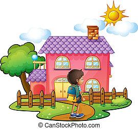 Ein Junge vor dem großen rosa Haus