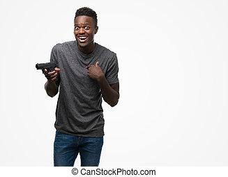 Ein junger afroamerikanischer Mann mit einer Waffe mit überraschendem Gesicht zeigt sich mit dem Finger auf sich selbst.
