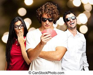 Ein junger Mann, der vor abstraktem Licht Poker mit Freunden spielt