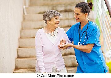Ein junger Pfleger, der Senioren hilft
