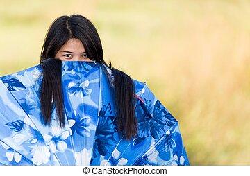 Ein junges Mädchen, das über ihren Regenschirm schaut.