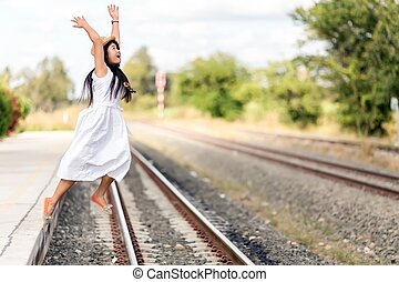 Ein junges Mädchen, das von einem Bahnsteig springt.
