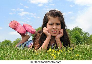 Ein junges Mädchen liegt auf dem Rasen