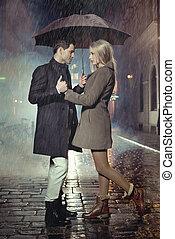 Ein junges Paar, das in starkem Regen posiert.