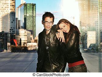 Ein junges Paar, das sich über den Hintergrund der Stadt stellt