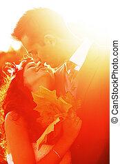 Ein junges Paar, das sich bei Sonnenuntergang küsst