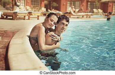Ein junges Paar, das sich im Schwimmbad küsst