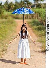 Ein junges Thai-Mädchen, das einen Regenschirm auf ihrem Kopf balanciert.