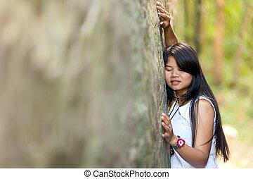 Ein junges Thai-Mädchen mit einem Stein.
