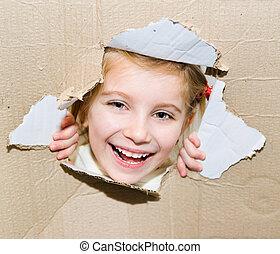 Ein Kind in einem zerrissenen Papierloch