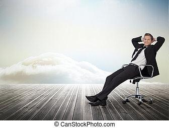 Ein lächelnder Geschäftsmann sitzt in einem Drehstuhl