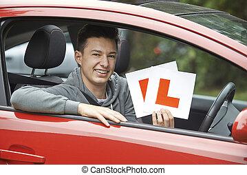 Ein lächelnder Teenager im Auto bei der Führerscheinprüfung.