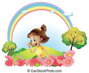 Ein lächelndes Mädchen im Garten mit rosa blühenden Blumen