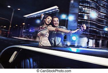 Ein lächelndes Paar im Hintergrund der Nachtstadt