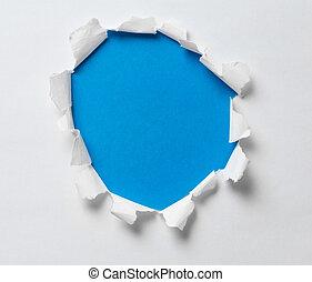 Ein Loch auf dem Papier mit blauem Hintergrund