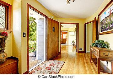 Ein luxuriöser Hauseingang mit Kunst und gelben Wänden.