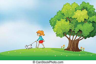 Ein Mädchen, das mit ihrem Hund auf dem Hügel läuft.