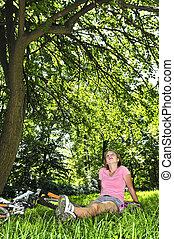 Ein Mädchen mit dem Fahrrad entspannt sich im Park