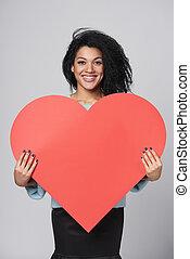 Ein Mädchen mit großer roter Herzform.