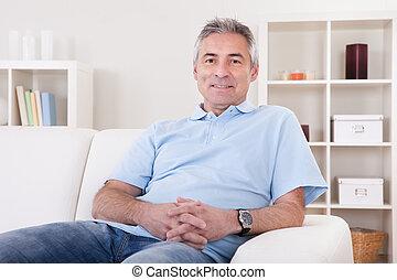 Ein Mann, der auf dem Sofa sitzt.