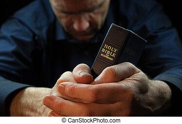 Ein Mann, der betet, eine heilige Bibel zu halten.