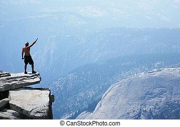Ein Mann, der mit erhobenem Arm auf einer Klippe steht