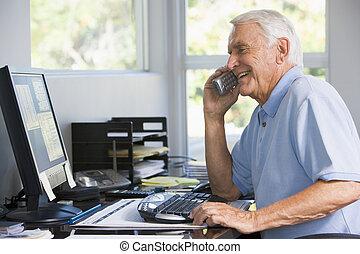 Ein Mann im Büro am Telefon, der Computer lächelt