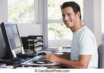 Ein Mann im Büro mit Computer und Lächeln.