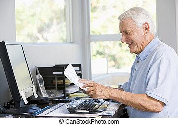 Ein Mann im Büro mit Computer und Papierkram, der lächelt