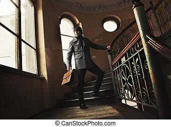 Ein Mann mit einem Aktenkoffer in einem alten Innenraum