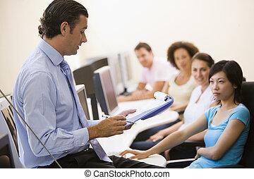 Ein Mann mit Klemmbrett, der eine Vorlesung im Computerunterricht hält